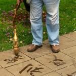 Kunming, Green Lake Park, pan kaligrafuje na chodniku